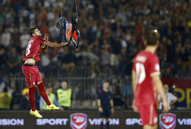 Serberen Stefan Mitrovic får fat i fanen, som den albanske premierministers bror styrede ned over banen. Øjeblikket efter endte kampen i kaos med spillerslagsmål og tilskuere på banen.