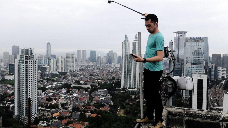 Arkivfoto. 2016. En mand fra Indonesien har snydt sig op i toppen af en skyskraper i Jakarta for at tage det perfekte billede. Han er en del af en gruppe af unge som dyrker at tage selfies på farlige steder.