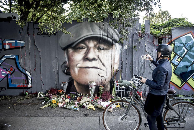 Blomster, øl, smøger og hilsner er lagt foran det portræt, der er blevet malet på hegnet ind mod Christiania på Prinsessegade i København til ære for Kim Larsen.