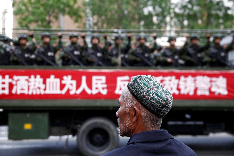 En Uighur ser til, mens paramilitære betjente køre gennem gaderne i en by i Xinjiang.