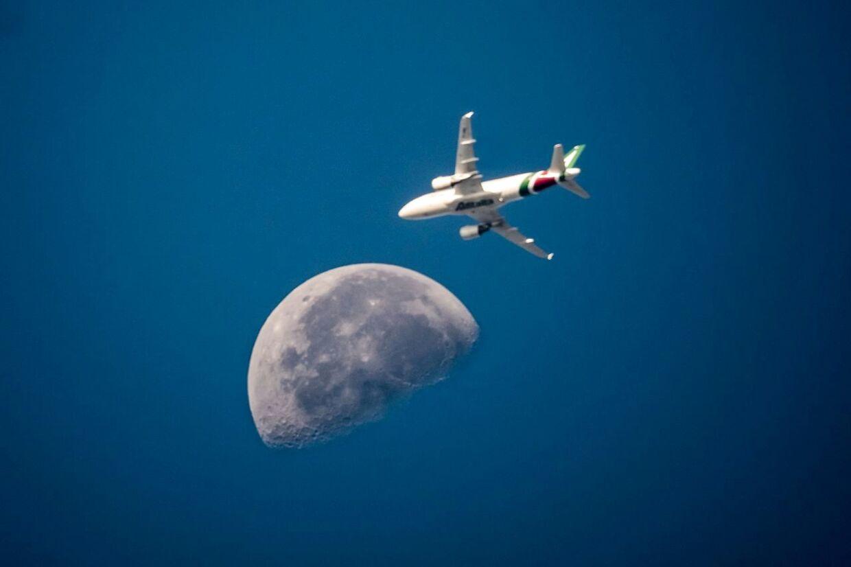Her ses et italiensk Alitalia-fly med månen i baggrunden over Rom 3. august 2018.