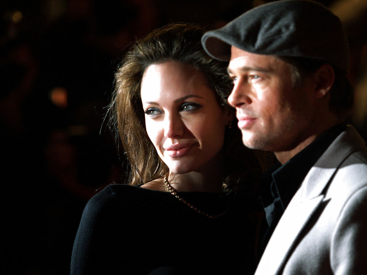 """US actress Angelina Jolie arrives with actor Brad Pitt in London's Leicester Square, 11 November 2007, to attend the European Premiere of her latest film, Beowulf. Jolie will plays an evil queen in the epic """"Beowulf, """" directed by Robert Zemeckis and distributed by Paramount and Warner Bros. MAX NASH / AFP"""