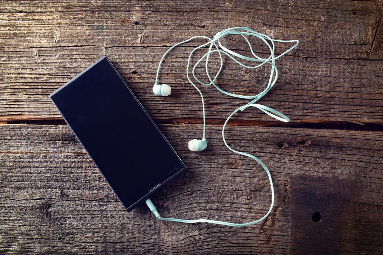 Mobiltelefon med høretelefoner (Arkivfoto).