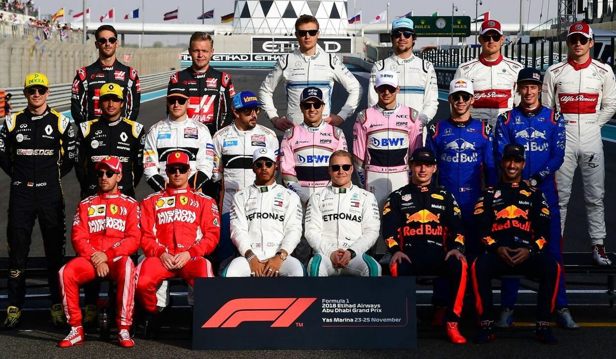 Formula One drivers, front row L-R: Ferrari's German driver Sebastian Vettel, Ferrari's Finnish driver Kimi Raikkonen, Mercedes' British driver Lewis Hamilton, Mercedes' Finnish driver Valtteri Bottas, Red Bull's Dutch driver Max Verstappen, Red Bull's Australian driver Daniel Ricciardo, middle row (L-R) Renault's German driver Nico Hulkenberg, Renault's Spanish driver Carlos Sainz, McLaren's Belgian driver Stoffel Vandoorne, McLaren's Spanish driver Fernando Alonso, Force India's Mexican driver Sergio Perez, Force India's French driver Esteban Ocon, Toro Rosso's French driver Pierre Gasly, Toro Rosso's New Zealand driver Brendon Hartley, (top row L-R) Haas French driver Romain Grosjean, Haas Danish driver Kevin Magnussen, Williams Russian driver Sergey Sirotkin, Williams' Canadian driver Lance Stroll, Alfa Romeo Sauber F1's Swedish driver Marcus Ericsson and Alfa Romeo Sauber F1's Monaco's driver Charles Leclerc pose for a photo prior to the Abu Dhabi Formula One Grand Prix at the Yas Marina circuit on November 25, 2018, in Abu Dhabi. (Photo by Giuseppe CACACE / AFP)