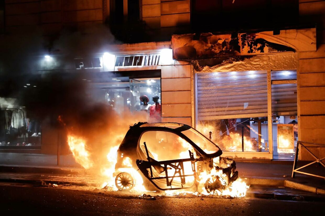 """A car burns during a protest of """"yellow vests"""" (gilets jaunes) against rising costs of living near Paris city Hall on December 8, 2018. - Paris was on high alert on December 8 with major security measures in place ahead of fresh """"yellow vest"""" protests which authorities fear could turn violent for a second weekend in a row. (Photo by Thomas SAMSON / AFP)"""