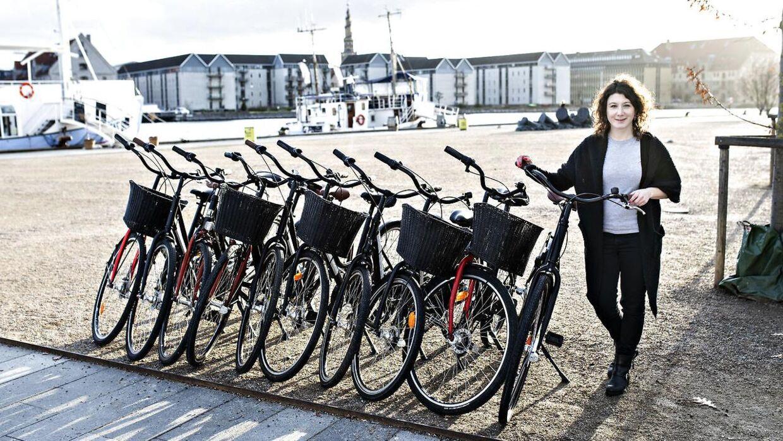 Yael Bassan fremviser, hvor meget 10 cykler fylder på pladsen foran Copenhagen Bicycles ved Nyhavn i København.