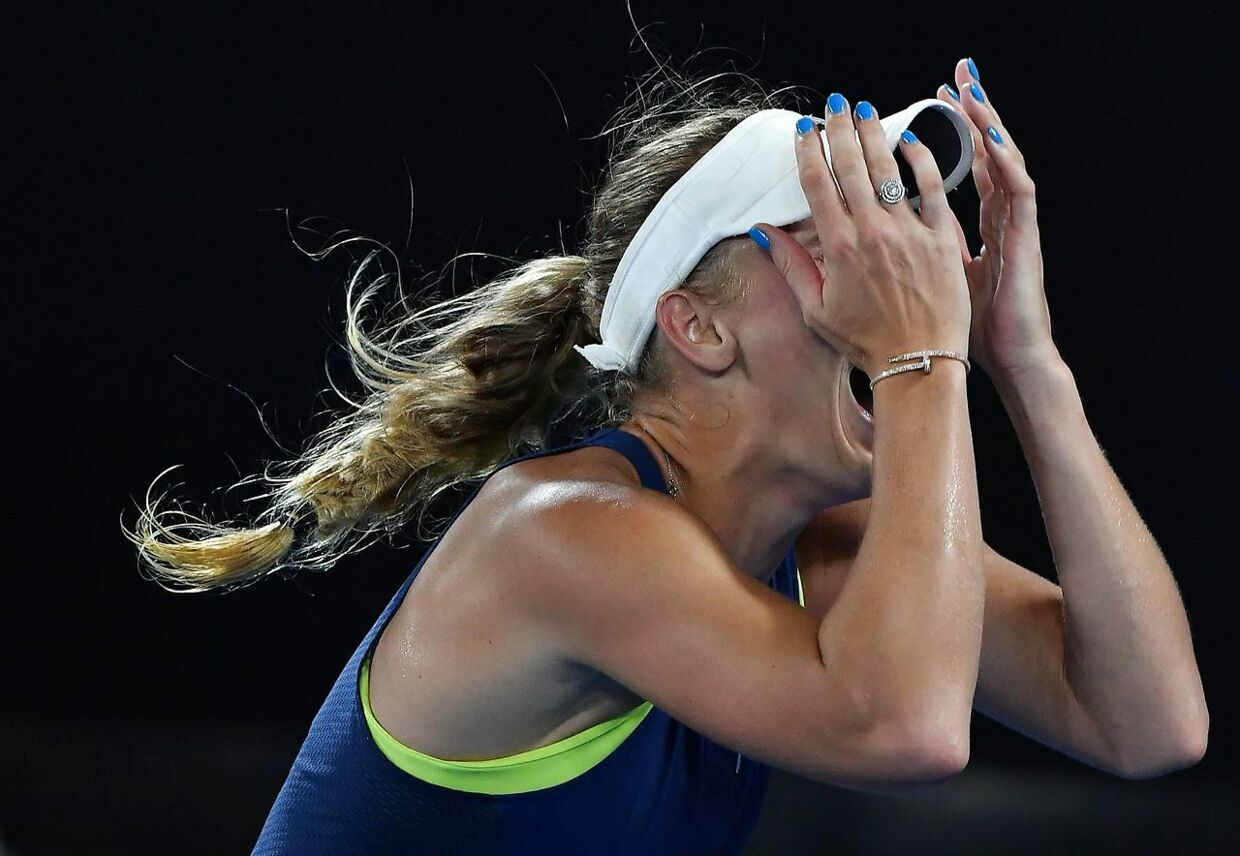 TOPSHOT - Denmark's Caroline Wozniacki celebrates beating Romania's Simona Halep in their women's singles final match on day 13 of the Australian Open tennis tournament in Melbourne on January 27, 2018. / AFP PHOTO / Greg Wood / - - IMAGE RESTRICTED TO EDITORIAL USE - STRICTLY NO COMMERCIAL USE - -