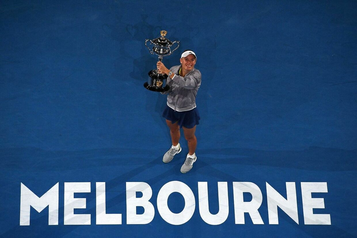 Denmark's Caroline Wozniacki celebrates with the championship trophy during the awards ceremony after her victory against Romania's Simona Halep in the women's singles final on day 13 of the Australian Open tennis tournament in Melbourne on January 27, 2018. / AFP PHOTO / WILLIAM WEST / - - IMAGE RESTRICTED TO EDITORIAL USE - STRICTLY NO COMMERCIAL USE - -