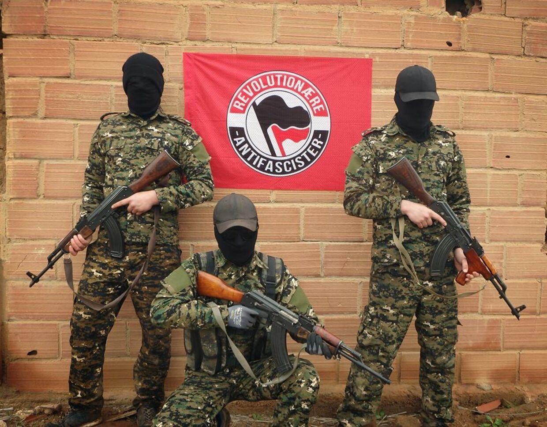 Tre maskerede personer, der angiveligt er danskere fra den yderste venstrefløj, poserer med Kalashnikow-geværer.