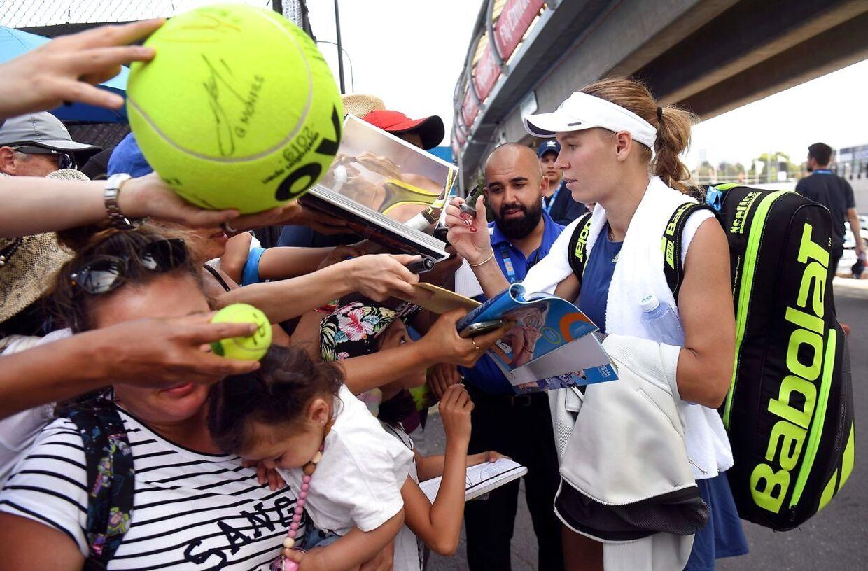 Caroline Wozniacki skriver autografer efter lørdagens træning i Melbourne.