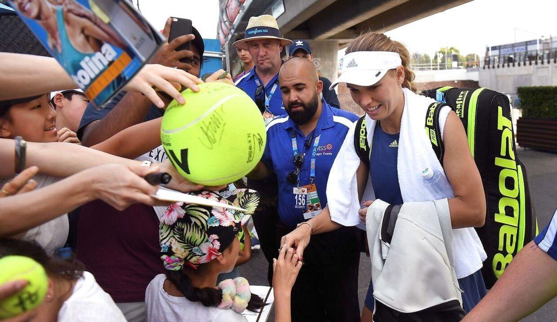 Caroline Wozniacki skriver autografer efter lørdagens træningspas i Melbourne Park forud Australian Open, der indledes mandag.