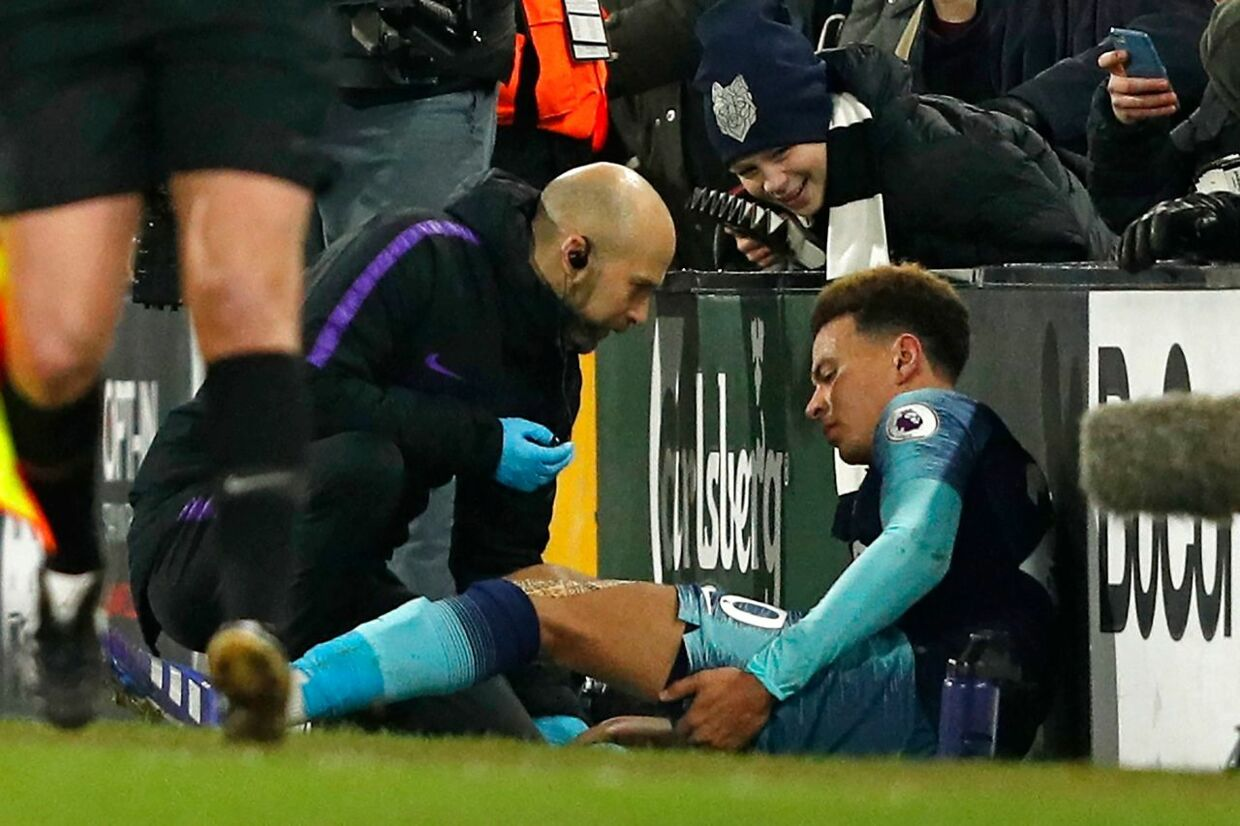 Tottenham Hotspur's English midfielder Dele Alli (R) receives medical attention as he holds his leg after appearing to pick up an injury during the English Premier League football match between Fulham and Tottenham Hotspur at Craven Cottage in London on January 20, 2019. (Photo by Adrian DENNIS / AFP) / RESTRICTED TO EDITORIAL USE.No use with unauthorized audio, video, data, fixture lists, club/league logos or 'live' services. Online in-match use limited to 120 images. An additional 40 images may be used in extra time.No video emulation. Social media in-match use limited to 120 images. An additional 40 images may be used in extra time.No use in betting publications, games or single club/league/player publications. /