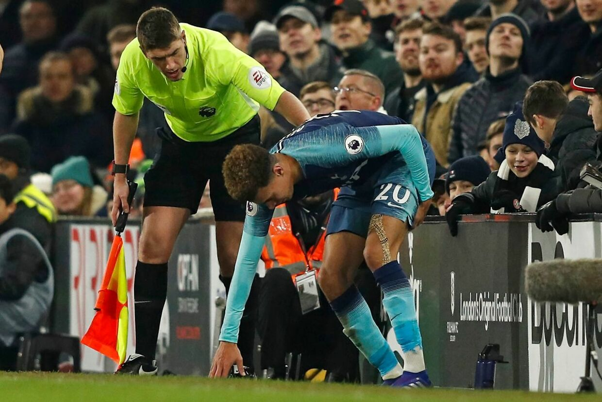 Tottenham Hotspur's English midfielder Dele Alli (R) holds his leg after appearing to pick up an injury during the English Premier League football match between Fulham and Tottenham Hotspur at Craven Cottage in London on January 20, 2019. (Photo by Adrian DENNIS / AFP) / RESTRICTED TO EDITORIAL USE.No use with unauthorized audio, video, data, fixture lists, club/league logos or 'live' services. Online in-match use limited to 120 images. An additional 40 images may be used in extra time.No video emulation. Social media in-match use limited to 120 images. An additional 40 images may be used in extra time.No use in betting publications, games or single club/league/player publications. /