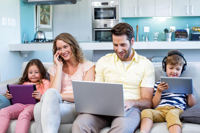 Hele familien kan sagtens være sammen, selv om hver især er optaget af sin egen digitale underholdning. (Foto: Scanpix)