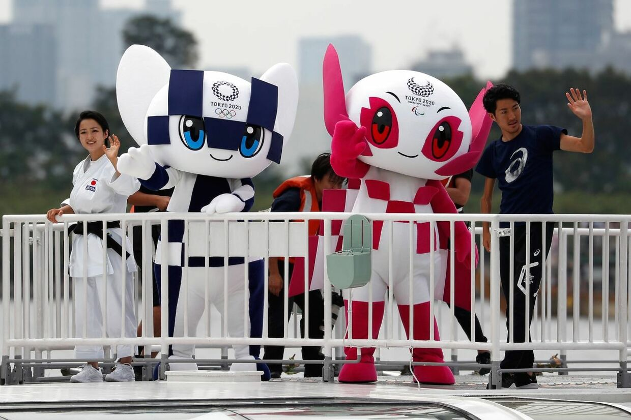Tokyo 2020 Olympic Games mascot Miraitowa (2nd L) and Paralympic mascot Someity wave with Japanese paralympic long-jumper Hajimu Ashida (R) and karateka Kiyo Shimkizu from a cruise ship during a parade upon their arrival at Odaiba Marine Park in Tokyo on July 22, 2018. Japanese organisers formally introduced their doe-eyed 2020 Olympic mascots to the world on July 22, christening them with superhero names that could provide a tongue-twisting challenge to some. / AFP PHOTO / POOL / ISSEI KATO
