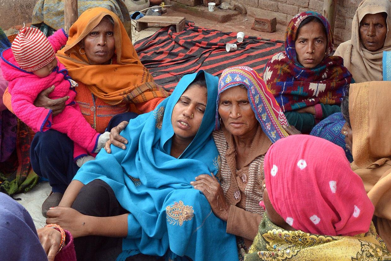 En kvinde bliver trøstet, efter at hendes mand er død som følge af at have drukket illegalt fremstillet alkohol i den nordlige del af delstaten Uttar Pradesh. Stringer/Reuters