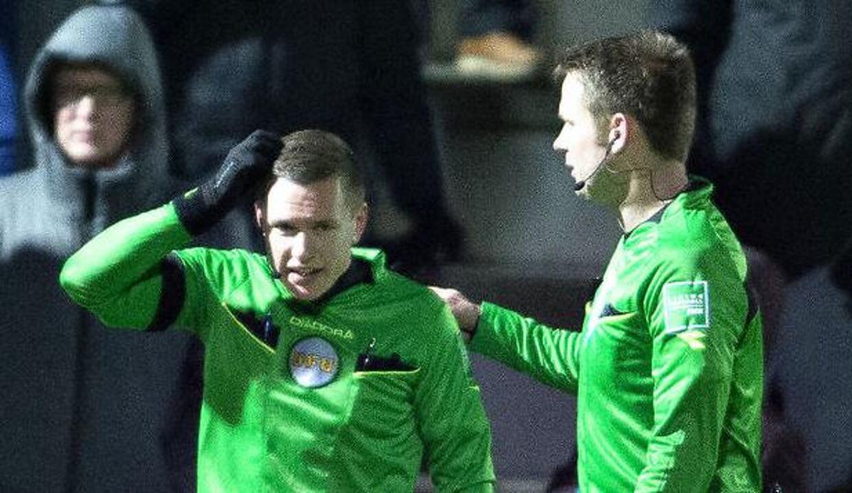 Liniedommer Henrik Hansen (tv) forklarer dommer Jens Maae, at han er blevet ramt af kasteskyts undervejs i mandag aftens Superliga-kamp i Hjørring mellem Vendsyssel FF og FC Midtjylland.