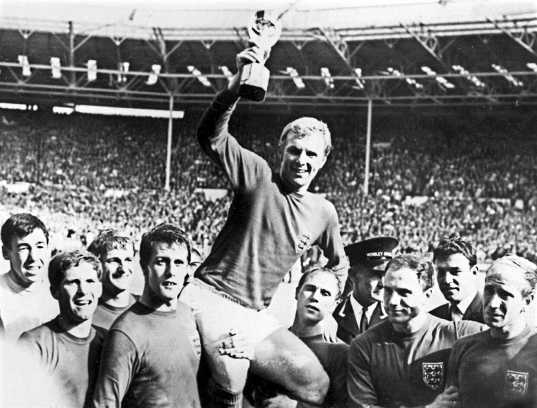 Den engelske anfører i 1966, Bobby Moore, løfter VM-trofæet i midten. Yderst fra venstre ses Gordon Banks, Alan Ball, Roger Hunt, Geoff Hurst, Ray Wilson, George Cohen og Bobby Charlton.