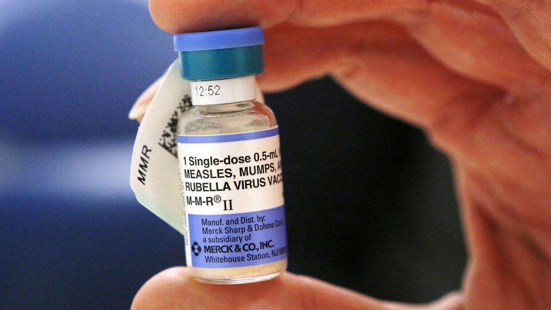 En sygeplejerske holder et glas med MFR-vaccine - mæslinger, fåresyge og røde hunde.