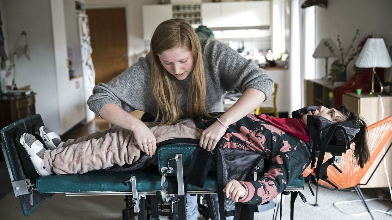 Hjælperen Louise placerer Liva i en maskine, hvor hun kan stå op. Det er vigtigt, at hun kommer op at stå, så hun ikke med tiden får knogleskørhed.