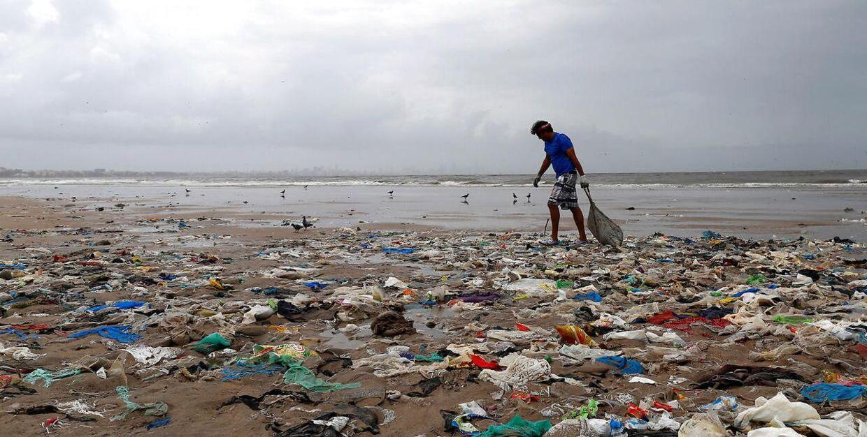 En frivillig samler affald på stranden i Mumbai, Indien. August 2016. REUTERS.