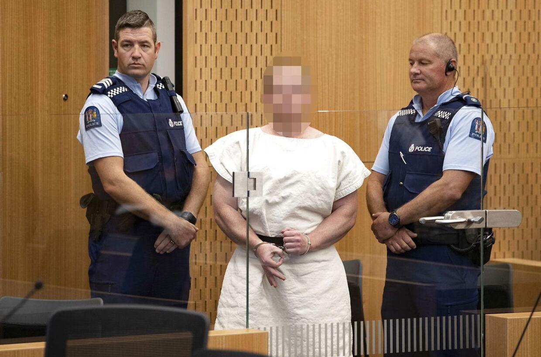 Brenton Harrison Tarrant føres ind i retssalen. På billedet ses han udføre det omstridte tegn.