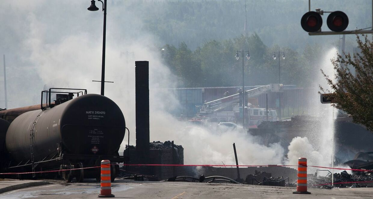"""(FILES) In this file photo taken on July 7, 2013 wreckage continues to burn after a freight train loaded with oil derailed July 6 in Lac-Megantic in Canada's Quebec province, sparking explosions that engulfed about 30 buildings in a wall of fire. - Netflix on January 22, 2019 has rejected a Quebec government request that it pull footage of a 2013 Canadian rail disaster from its film """"Bird Box, """" while apologizing for any pain it may have caused. In a letter to Quebec Culture Minister Nathalie Roy, Netflix also promised not to use the Lac Megantic crash footage in future productions. But it said the archival images of one of Canada's worst train derailments have been widely used in the film and television industry, and cannot be taken back. The 72-car train carrying shale oil came loose in the middle of the night, rolled down a hill unmanned, derailed and exploded in the centre of the picturesque lakeside town. It took firefighters two days to put out the blaze, which killed 47 people. (Photo by François Laplante-Delagrave / AFP)"""