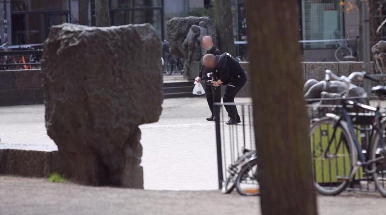 Her går betjente med den mistænkelige genstand i en hvid plastikpose.