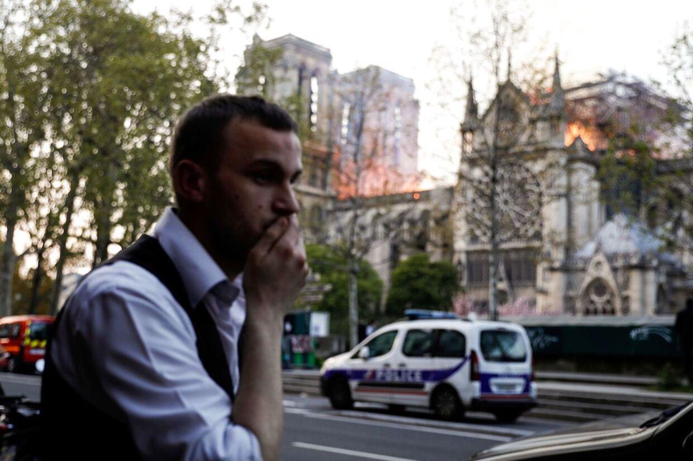 En mand reagerer, da han ser flammerne stå ud af Notre Dame.