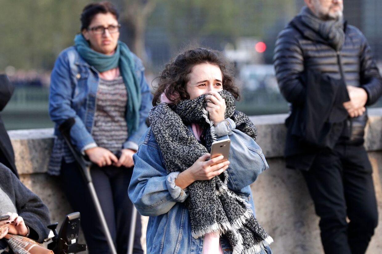 En ung kvinde ligner, at hun er ved at græde, mens hun kigger på brændende Notre Dame.