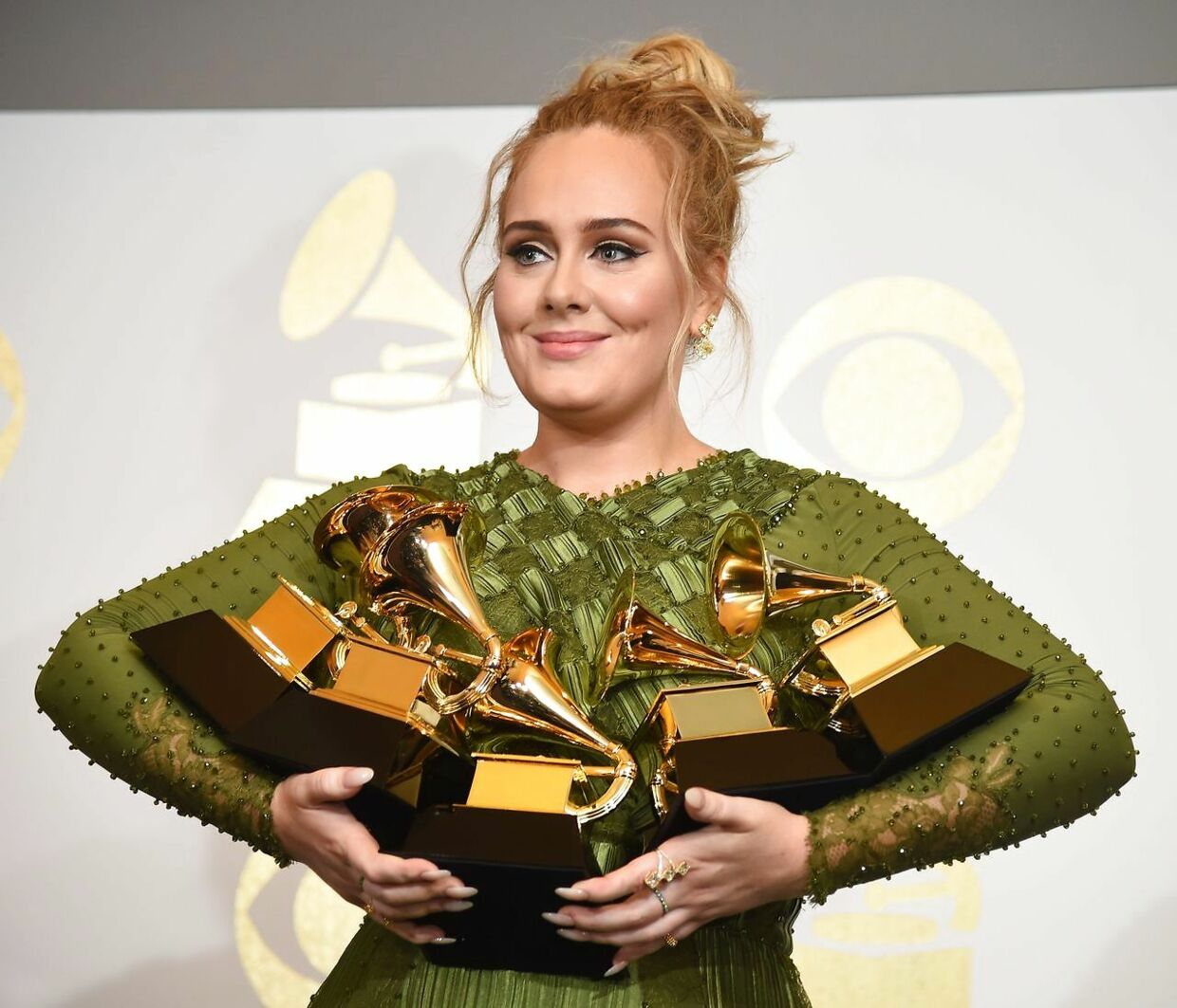 """(ARKIV) TOPSHOT - Adele poses in the press room with her trophies, including the top two Grammys of Album and Record of the Year for her blockbuster hit """"Hello"""" and the album """"25"""", during the 59th Annual Grammy music Awards on February 12, 2017, in Los Angeles, California. Den engelske sanger Adele fylder 30 år lørdag den 5. maj 2018.. (Foto: ROBYN BECK/Ritzau Scanpix)"""