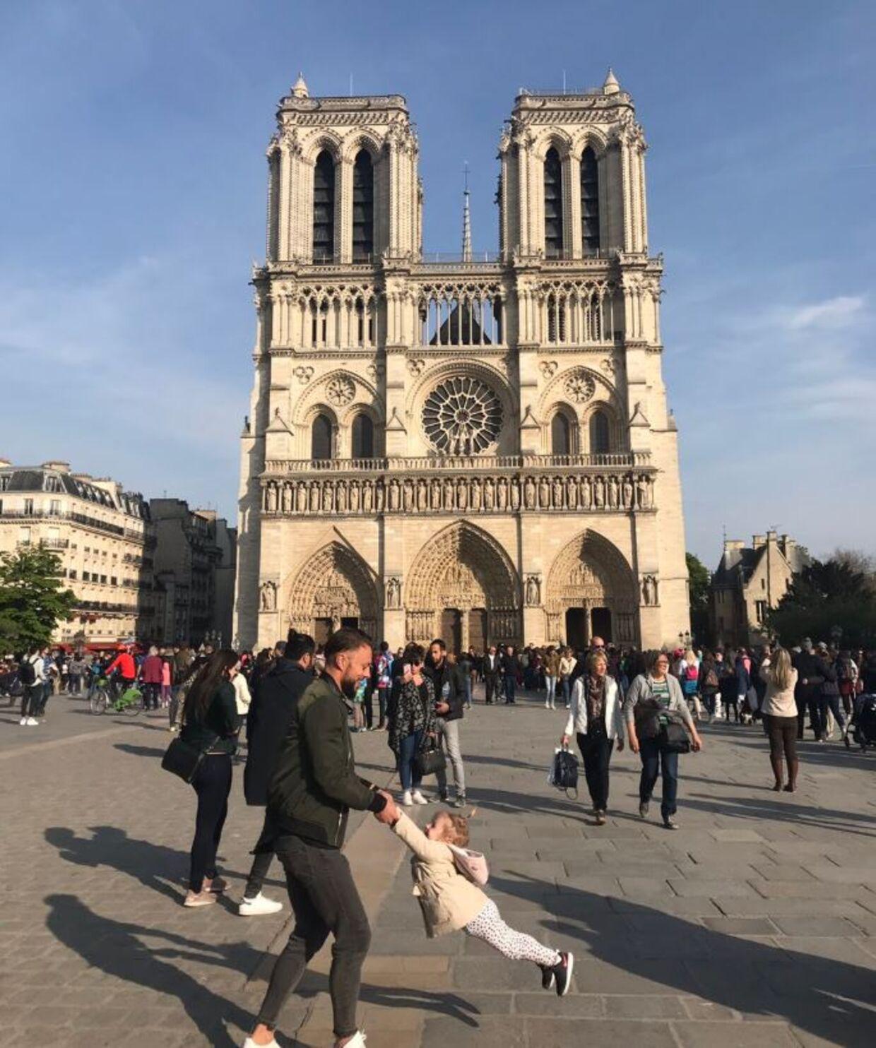 Dette billede gik verden rundt, efter at den ikoniske katedral Notre Dame brød i brand. Nu har fotografen fået kontakt til faren, der leger med sin datter på billedet. Det blev taget, blot en time før katedralen begyndte at brænde.