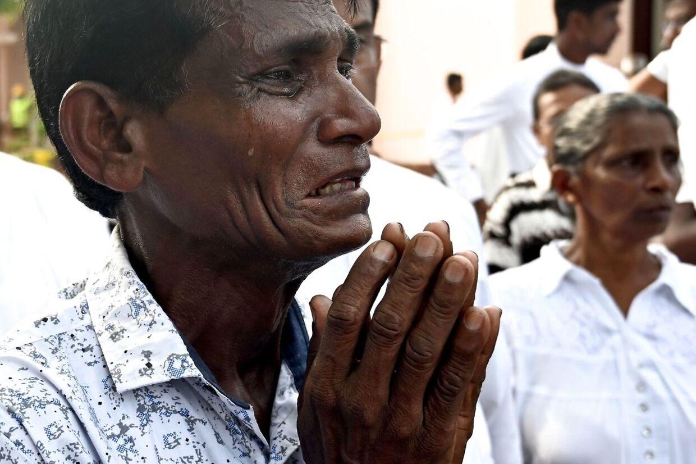 En mand græder, da han deltager i en massebegravelse ved St. Sebastian-kirken i Negombo.