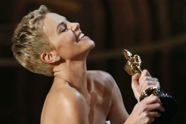 """Charlize Theron med Oscar-stauetten, hun senere overrakte til Quentin Tarantino for bedste manuskript for filmen """"Django Unchained""""."""