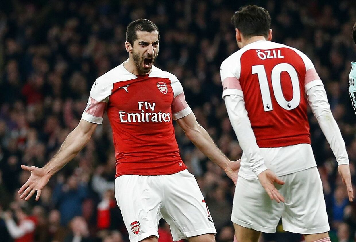Arsenal's Armenian midfielder Henrikh Mkhitaryan (L) celebrates scoring his team's second goal with Arsenal's German midfielder Mesut Ozil during the English Premier League football match between Arsenal and Bournemouth at the Emirates Stadium in London on February 27, 2019. (Photo by Ian KINGTON / AFP) / RESTRICTED TO EDITORIAL USE.No use with unauthorized audio, video, data, fixture lists, club/league logos or 'live' services. Online in-match use limited to 120 images. An additional 40 images may be used in extra time.No video emulation. Social media in-match use limited to 120 images. An additional 40 images may be used in extra time.No use in betting publications, games or single club/league/player publications. /