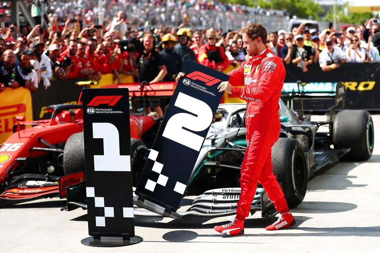 Sebastian Vettel sætter skiltet med '2' ud for Lewis Hamiltons racer.