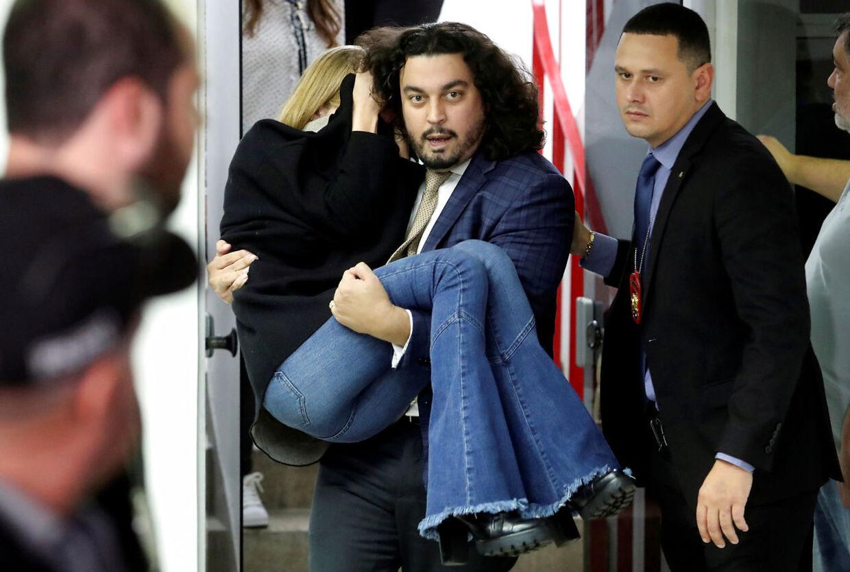 Advokat Danilo Garcia de Andrade bærer her Najila Trindade ud til sin bil, efter hun har afgivet vidneforklaring.