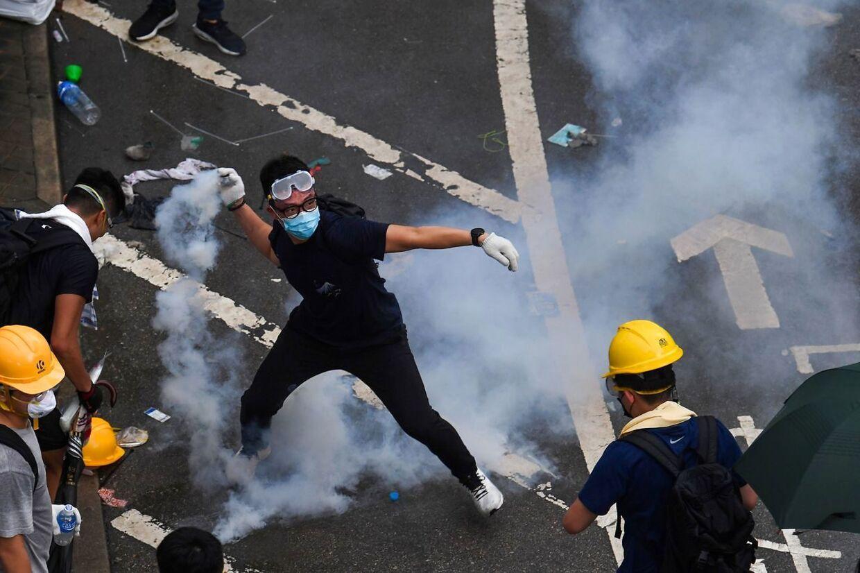 En demonstrant kaster med tåregas mod politiet.