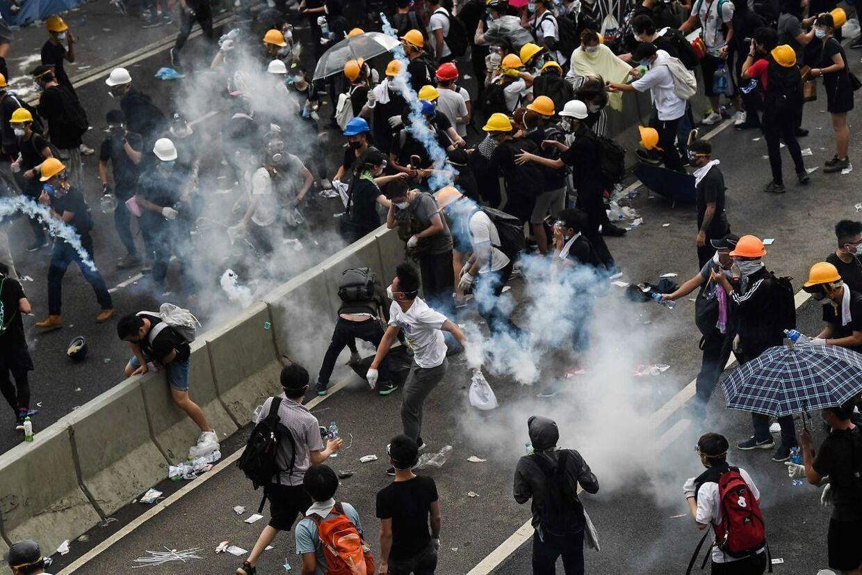 Demonstranter tørner sammen med politiet. Begge parter kaster med tåregas.