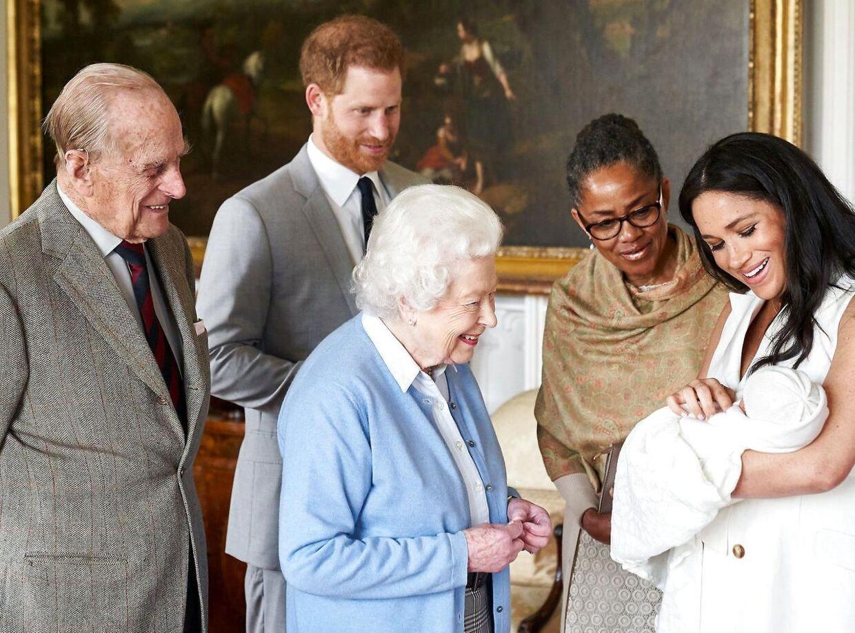 De stolte forældre viser den lille nye prins frem for Dronningen og prins Philip, mens også Meghans mor Doria Ragland ser til.