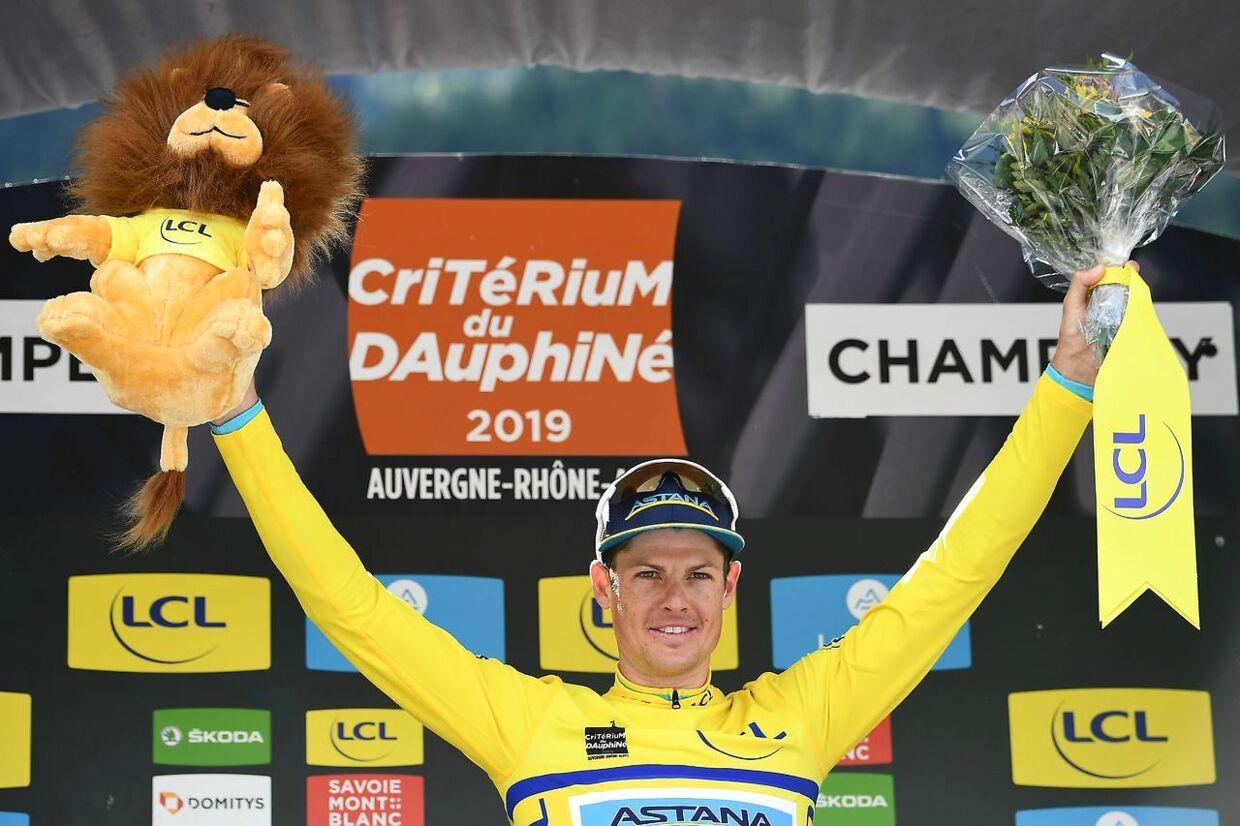 TOPSHOT - Astana Pro Team rider Denmark's Jakob Fuglsang celebrates his overall leader's yellow jersey on the podium of the eighth and last stage of the 71st edition of the Criterium du Dauphine cycling race, 113, 5 km between Cluses and Champery on June 16, 2019. (Photo by Anne-Christine POUJOULAT / AFP)
