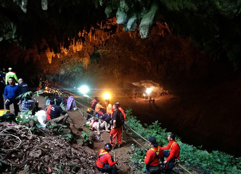 Ved indgangen til grotten hviler nogle af redningsarbejderne sig. I 17 dage står redningsarbejdet på.