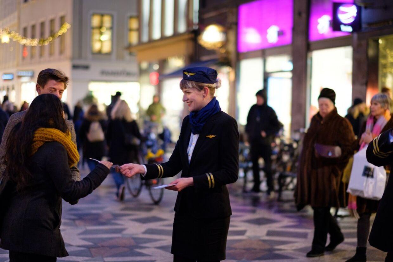 Aurelija Aniulyte ved aktion klædt ud som stewardesse og i gang med at dele boardingpasses ud til folk