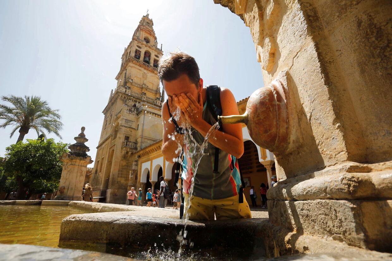 En turist snupper en tår vand fra en vandpost i den spanske by Cordoba.