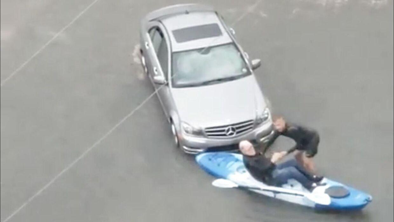 Da en mand strander i oversvømmelsen i sin sølvgrå Mercedes kommer en anden mand ham til undsætning i sin kajak. Billedet er fra torsdag.