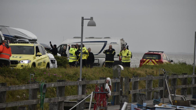Tilstede ved fjorden er politiet og ambulancer