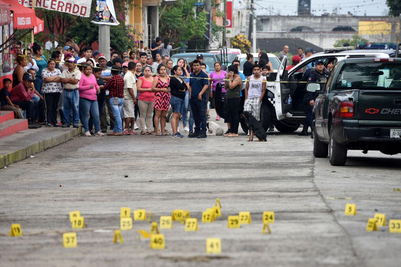 Bekymrede indbyggere i byen Tuzamapan ser til, mens lokalt politi undersøger et gerningssted, hvor flere blev dræbt i et skyderi 16. maj i år. Yahir Ceballos/Reuters