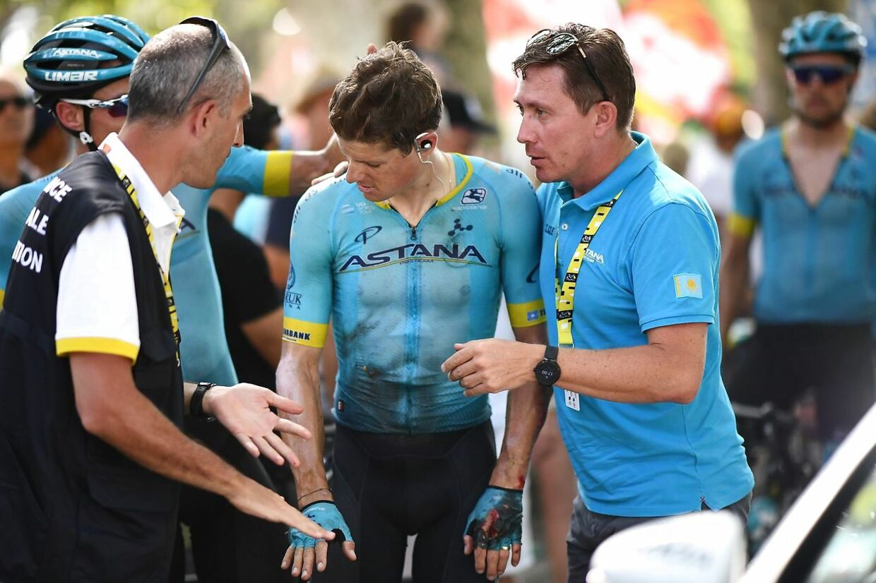 Denmark's Jakob Fuglsang (C) is comforted after a fall during the sixteenth stage of the 106th edition of the Tour de France cycling race between Nimes and Nimes, in Nimes, on July 23, 2019. (Photo by Anne-Christine POUJOULAT / AFP)