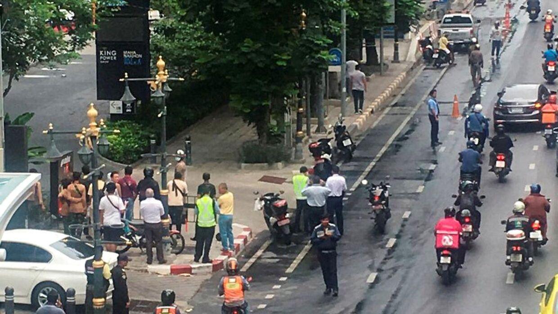En mindre menneskemængde forsamlet i nærheden af en eksplosionerne i Bangkok.