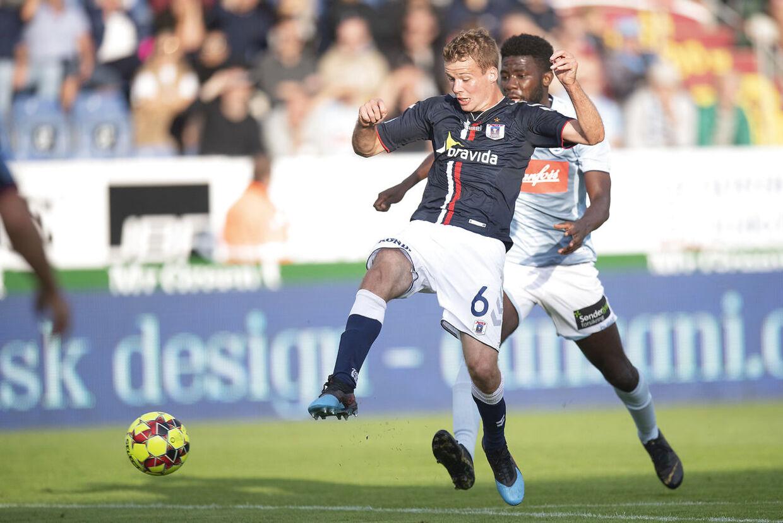 AGF's Nicolai Poulsen tackles af Sønderjyske-spiller i mandag aftens Superliga-kamp.